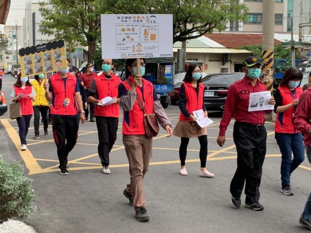 區長帶領有一群身穿粉紅色背心的人員向民眾宣導3