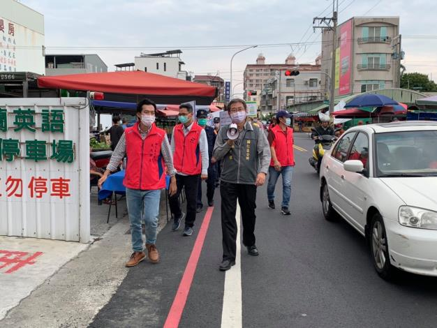 區長帶領有一群身穿粉紅色背心的人員向民眾宣導2
