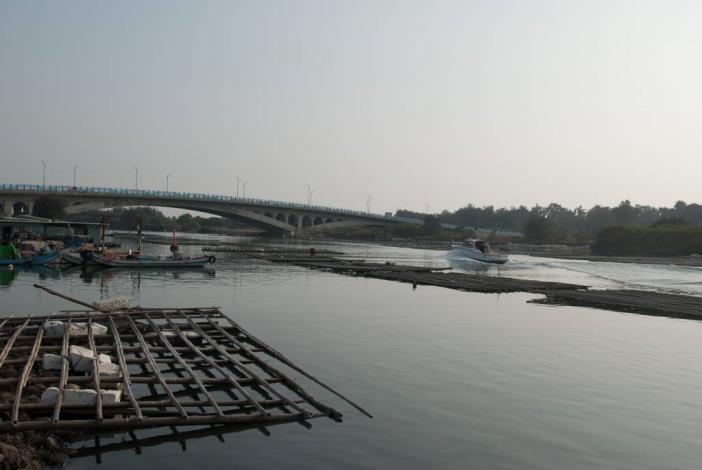 過由路邊岸上拍漁光大橋全景有遊艇行駛而過