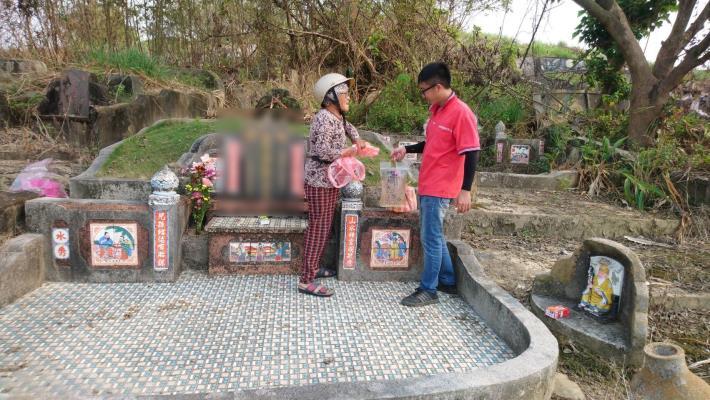 民眾趁周末來掃墓,孫子拿取水袋給奶奶