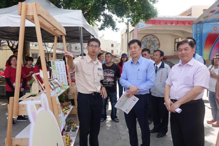 役男為陳次長介紹他們的社區營造作品成果.JPG