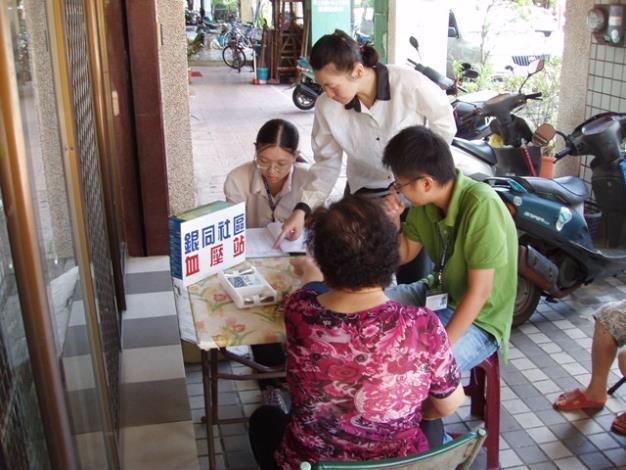 同學在志工的協助指導下學習血壓量測服務