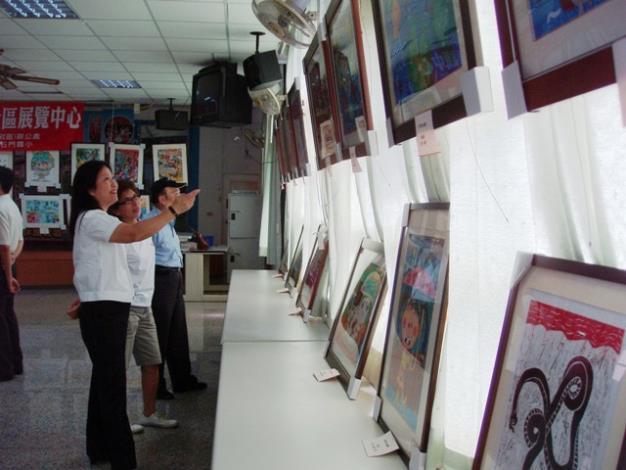 黎區長與西湖里志工一起欣賞學生畫作