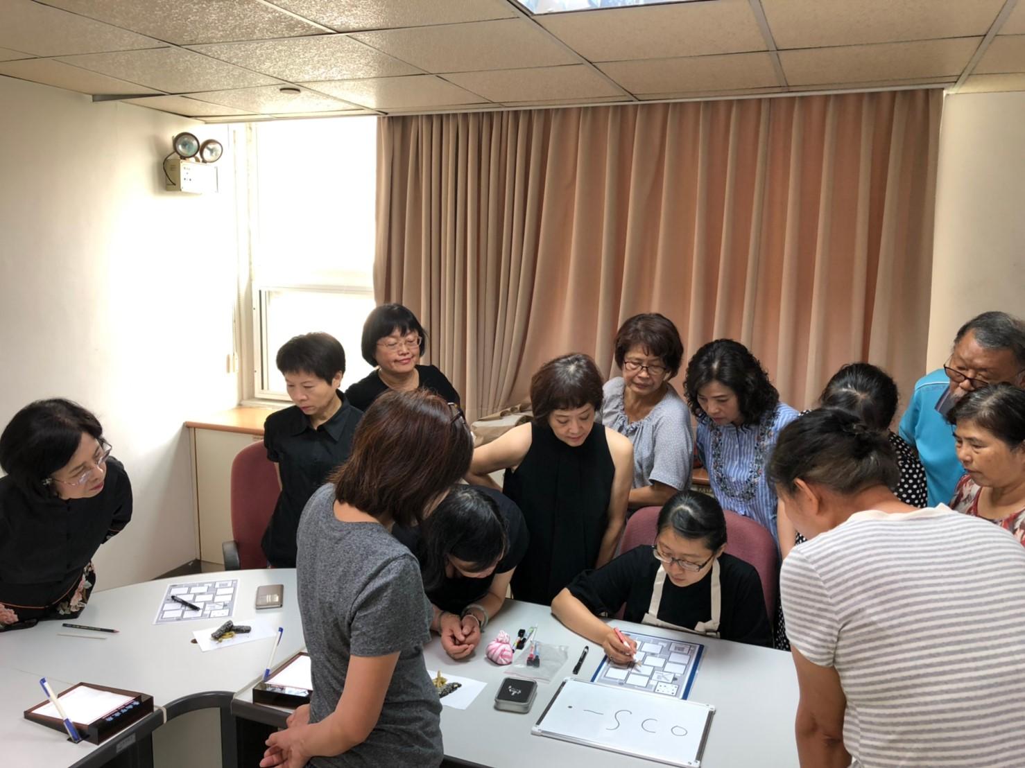 禪繞畫老師正認真的教導家防中心志工伙伴們如何畫出細緻的作品