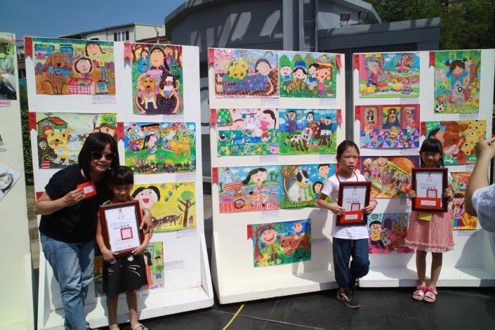 圖2  得獎學生和家長與得獎作品合影留念。
