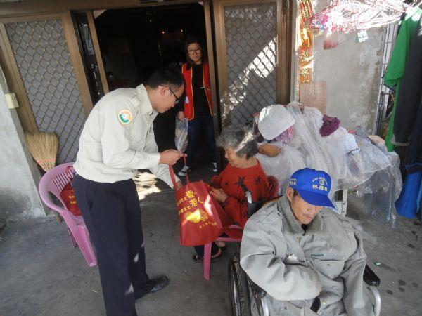 替代役男向年長老夫妻介紹致贈年菜包內容物